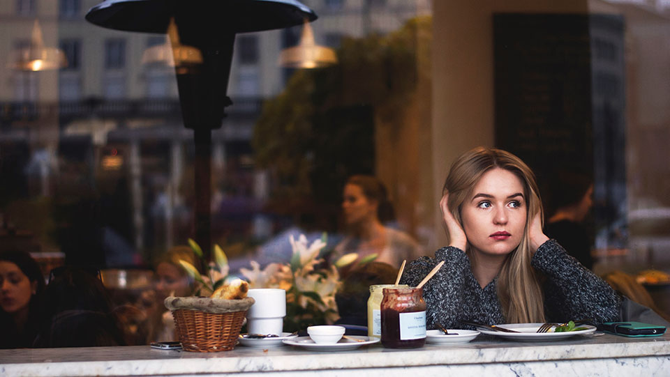 Young woman staring out of a cafe window on her own