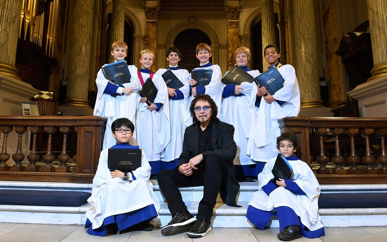 Tony Iommi sitting down surrounded by Birmingham Cathedral choir