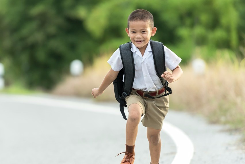 School boys runs home from school with ruck sack on his back