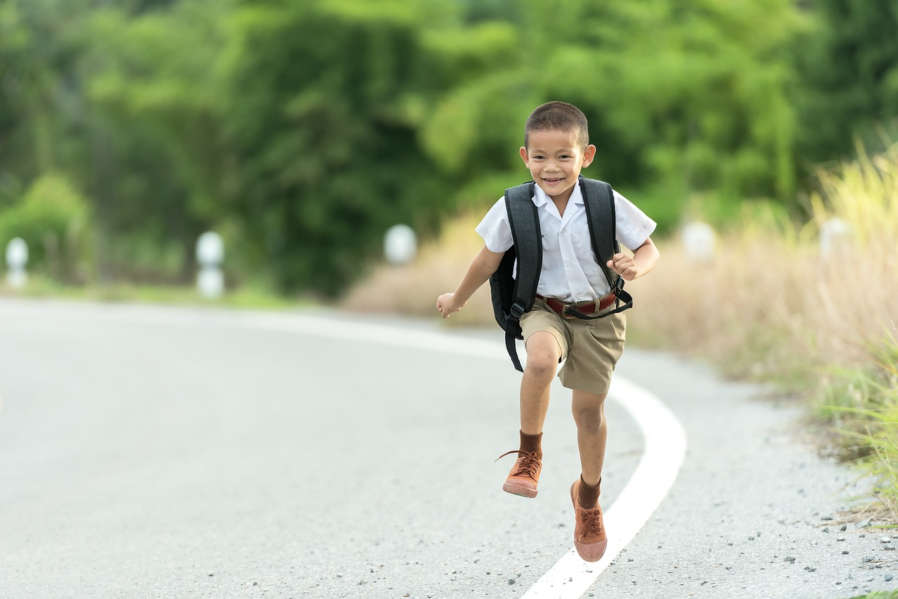 School boy runs home with ruck sack on his back